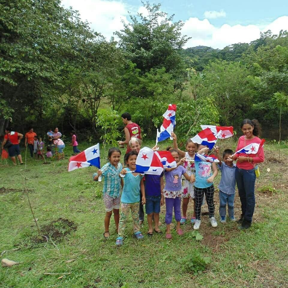 Children from a nearby community waving Panamanian flags during the National Tree Reforestation Program - Cerro Chucantí.